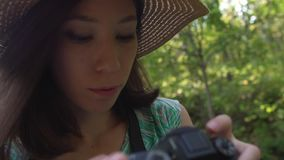 A girl in straw hat and dress walks through the park and photographs nature. stock footage