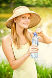 Girl in straw hat drinks water Royalty Free Stock Photography