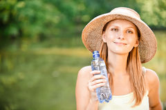 Girl in straw hat drinks water Royalty Free Stock Photo