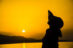 A girl with straw hat enjoy on sunset Stock Photography