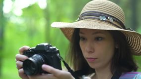 Girl in straw hat flips through photos on the camera. on nature. stock video
