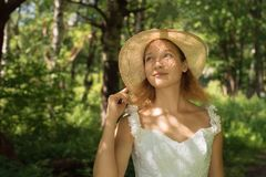 Girl in a straw hat in the forest on a sunny day Stock Photos