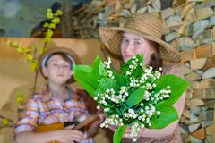 A girl in a straw hat holding a bouquet of lilies of the valley with a guy royalty free stock image
