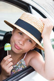 Girl in straw hat and with lolipop. In summer Royalty Free Stock Photography
