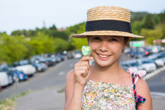 Girl in straw hat and with lolipop. In summer Stock Photo