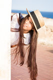 Girl in straw hat peeks out from behind wall. In summer stock images