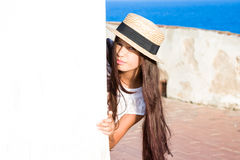 Girl in straw hat peeks out from behind wall. In summer stock image