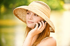 Girl in straw hat with phone Stock Image