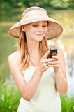 Girl in straw hat with phone Royalty Free Stock Photo