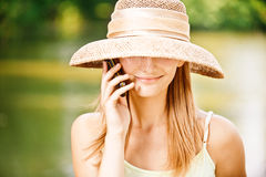 Girl in straw hat with phone Royalty Free Stock Image