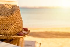 Girl in a straw hat reading a book on the beach of the red sea a symbol of relaxation. Girl in a straw hat reading a book on the beach of the red sea as a symbol Royalty Free Stock Images