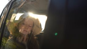 Girl Reading Book Inside Car in backseat. Girl with straw hat Reading Book Inside Car in backseat. road trip concept stock footage