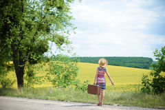 Girl in straw hat with retro suitcase near summer. Picture of girl in straw hat with retro suitcase near beautiful summer meadow. Backview of young woman Royalty Free Stock Images