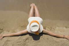 Girl with straw hat sitting on sandy beach Royalty Free Stock Image