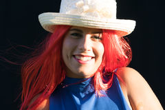 Girl with straw hat. She is smiling young woman with a wig of red hair Stock Image