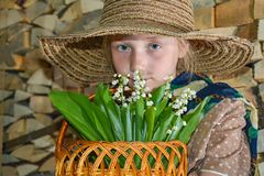A girl in a straw hat sniffs a bouquet with lilies of the valley on the background of firewood and logs.  royalty free stock photography