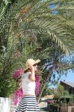Girl in straw hat under palm tree stock photo