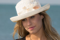 Girl with straw hat. A young woman with a white hat at sea Royalty Free Stock Photo