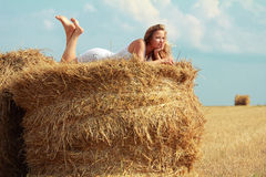 Girl on straw roll Royalty Free Stock Images