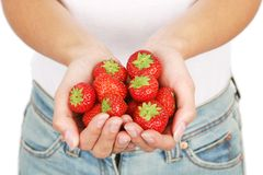 Girl With Strawberries. Young and attractive girl holding strawberries. Isolated on white. Shallow DOF, focus on strawberries Royalty Free Stock Images