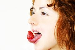 Girl and strawberry. Strawberry on the tongue Stock Photos