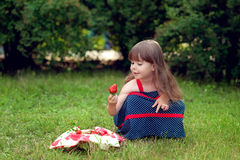 Girl with strawberry. In hand royalty free stock photos