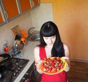 Girl with strawberry on the kitchen Royalty Free Stock Photo