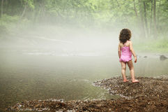 Girl beside a stream Stock Image