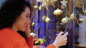 Girl streaming live. Young smiling curly woman looking at phone on the background of Christmas decor. Videocall, streaming live. Girl in a red sweater and with stock video footage