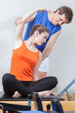 Girl streching in the gym. Pretty girls streching with her teacher Royalty Free Stock Photos