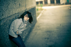 Girl on the street. Girl standing at the wall in windy weather Royalty Free Stock Photos