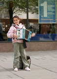 Girl in the street with accordion Royalty Free Stock Images