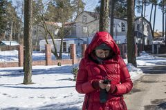 Girl on the street with a mobile phone in winter. A girl in a red jacket with a mobile phone in the winter in the park Royalty Free Stock Image