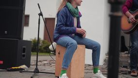 Girl street musician sitting on a subwoofer and stomps his feet and claps his hands. Girl percussionist. Speech street rock band stock video footage