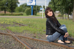 The girl on the street. Is sitting on the rails Royalty Free Stock Images
