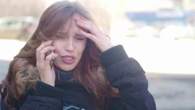 The girl on the street talking on the phone. quarrels and gets upset