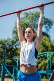 Girl on street workout. She pull-ups herself up on bar on sports ground in park royalty free stock photo