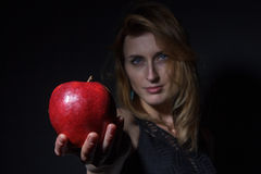 Girl stretches an apple to the camera Stock Photography