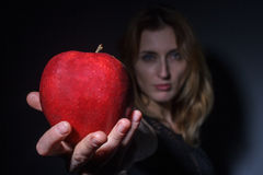 Girl stretches an apple to the camera Royalty Free Stock Photo