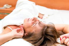Girl stretches awake in bed in morning Royalty Free Stock Image