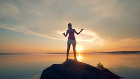 Sportswoman warms up on a rock near lake. A girl stretches her body before running on a sunset background. A girl stretches her body before running on a sunset stock video footage