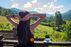 The girl stretches, looking at the morning sun and mountains. Next to her, on the railing of the balcony, is a cup of coffee.  royalty free stock image