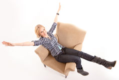 Girl stretching arms and legs on an armchair Stock Images