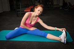Girl stretching in gym Stock Images