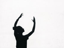 Girl stretching her hands toward the sky around on the white wall background Royalty Free Stock Photos