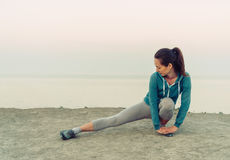 Girl stretching her legs on coast, wokout Stock Images
