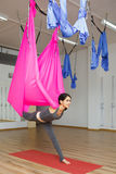 Girl stretching leg with help of hammock. Aerial exercise yoga Royalty Free Stock Photography