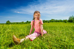 Girl stretching legs apart on grass Royalty Free Stock Photography