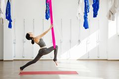 Girl stretching legs with help of hammock. Aerial exercise yoga royalty free stock images