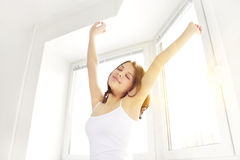 Girl stretching in the morning. Against the window Stock Images